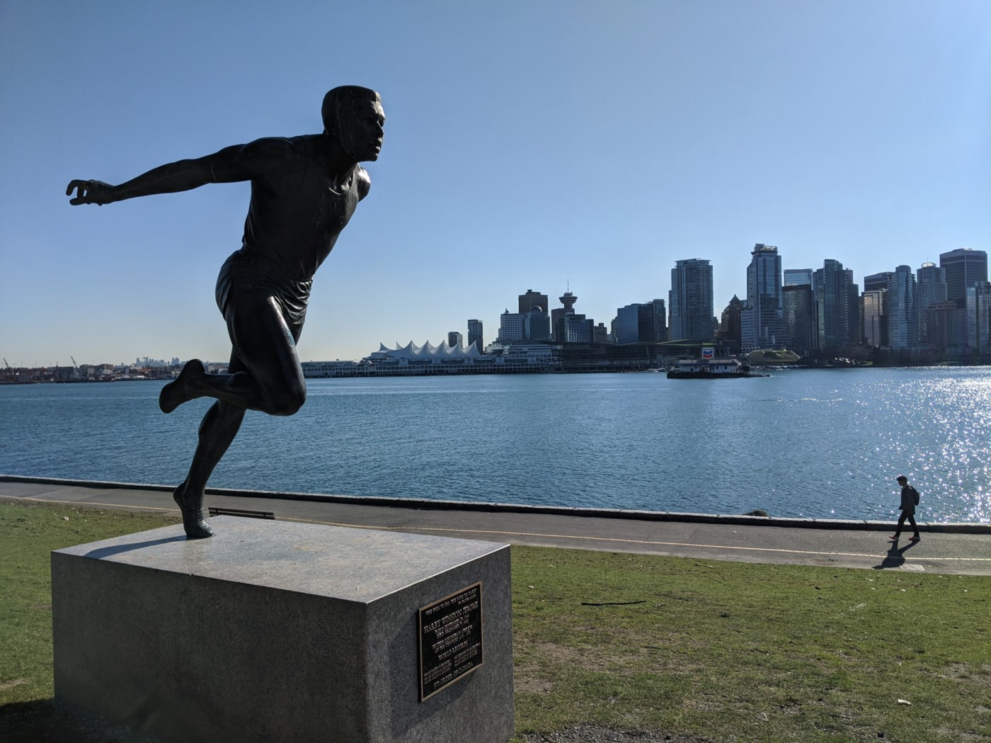 Photo of a man running on grass overlooking Vancouver