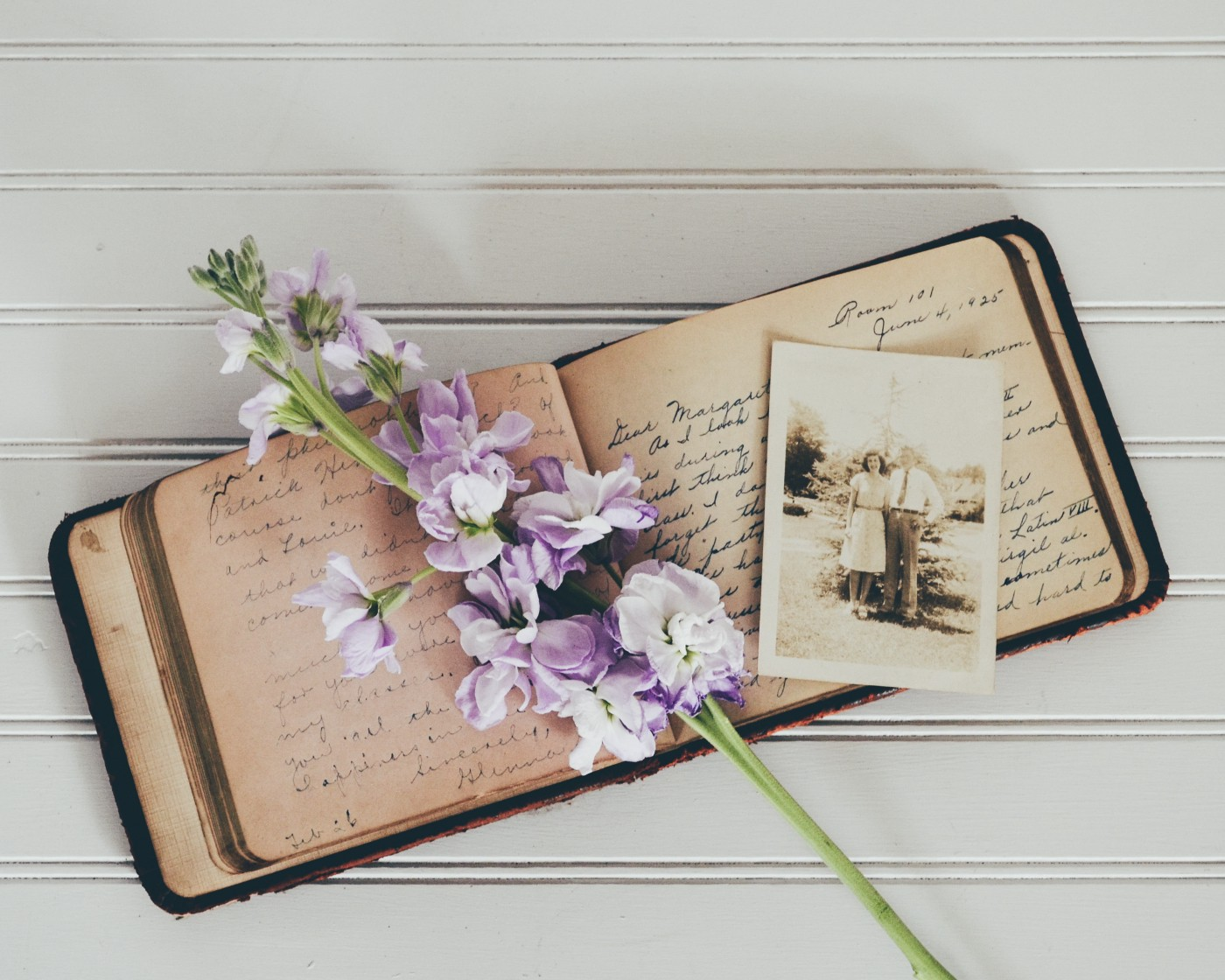 Old journal with handwritten text. A photo sits on top, it pictures a man and woman. Purple flowers also rest on top of it.