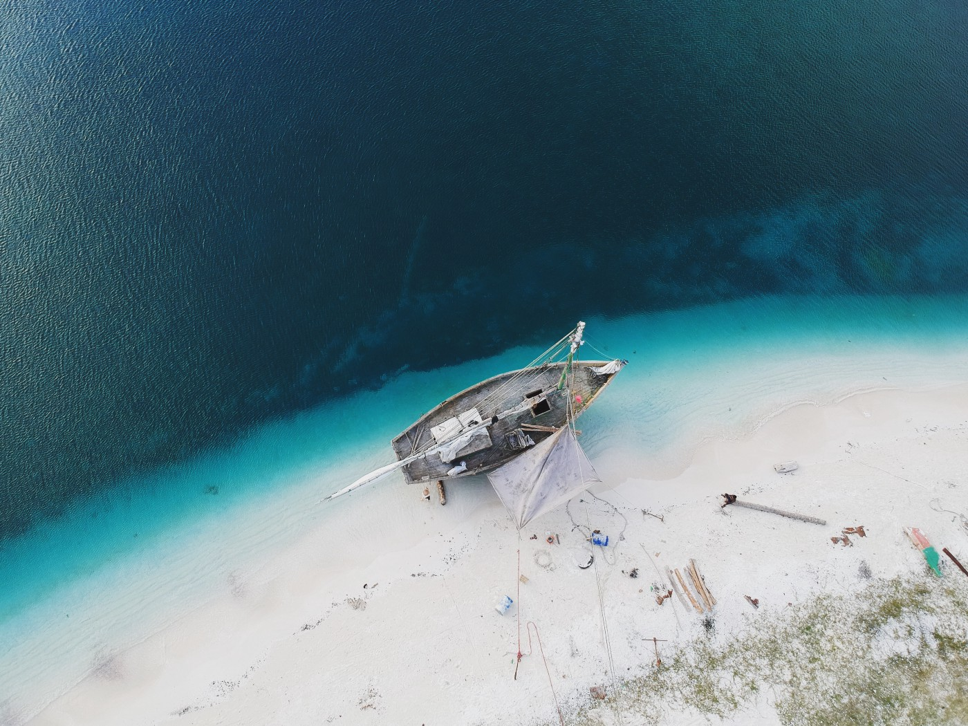 Aerial photo of a ship on a beach being worked on.