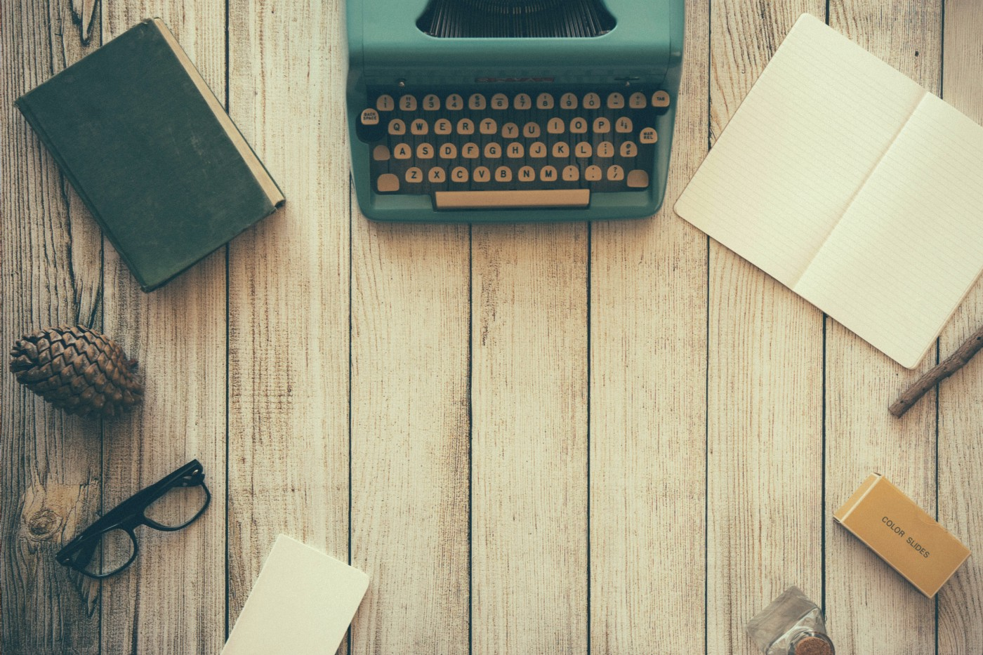 An antique typewriter sits on tabletop with book, glasses, journal, pinecone.