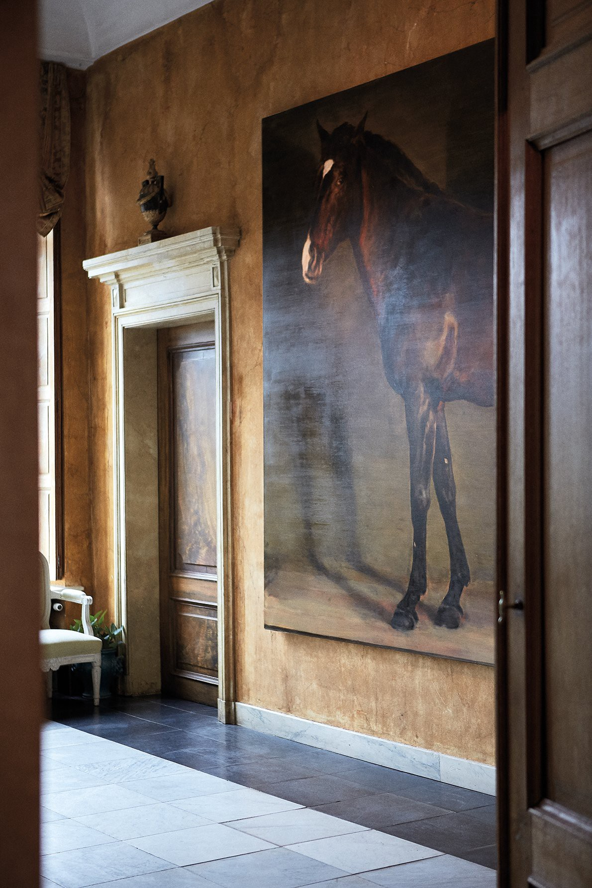 In the hallway hangs an oversized portrait of Axel's horse, Raio, painted by Michaël Borremans in 2015. (Photo: Mariluz Vidal, Living In)