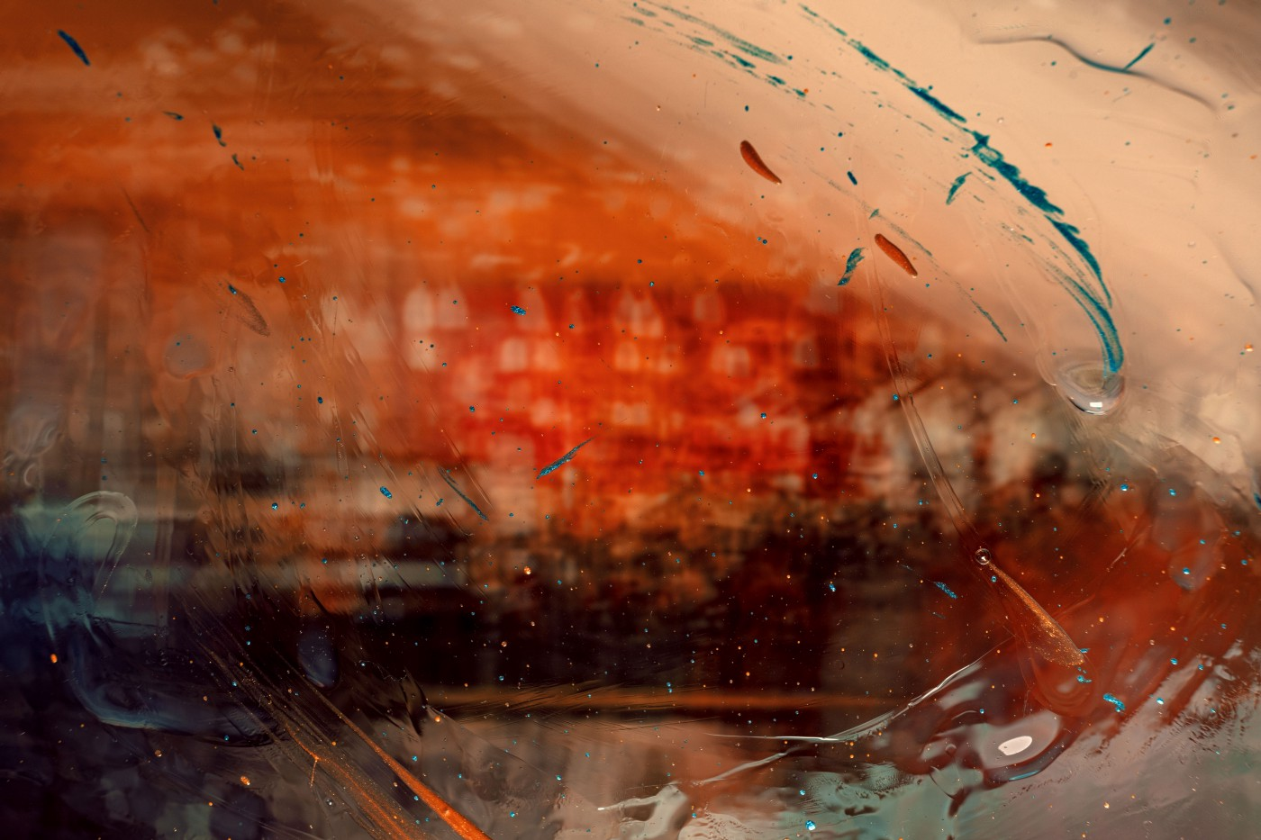 Abstract image of predominately red and cream colors with green and blue splatters, mixed media.