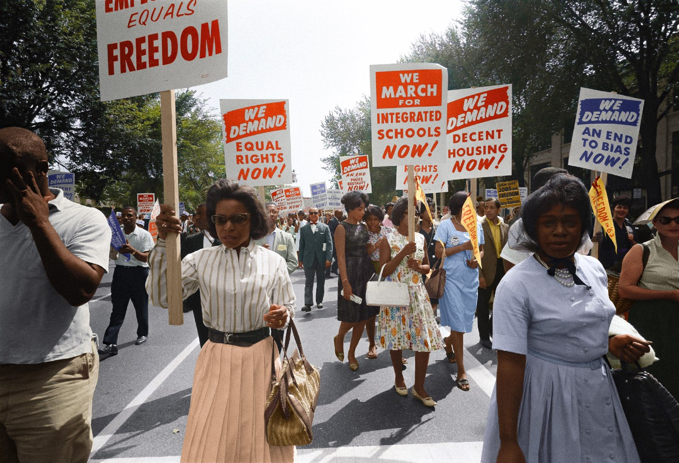 "Civil rights march on Washington, D.C. on August 28th, 1963. Women in foreground hold up signs reading: ""we demand equal rights now, we march for integrated schools now, we demand an end to bias now, and we demand decent housing now."""