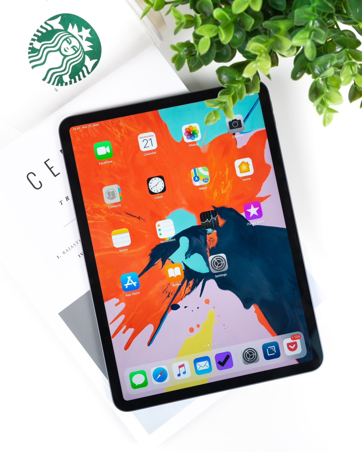 The new iPad Pro sitting on top of a book next to a cup of Starbucks in the top left corner and a decorative green plant in the top right corner.