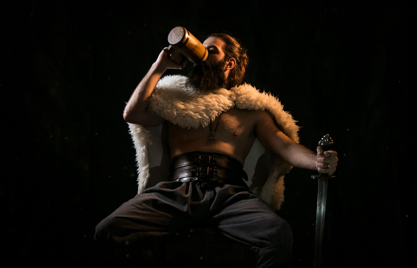 seated man guzzling ale and holding a sword