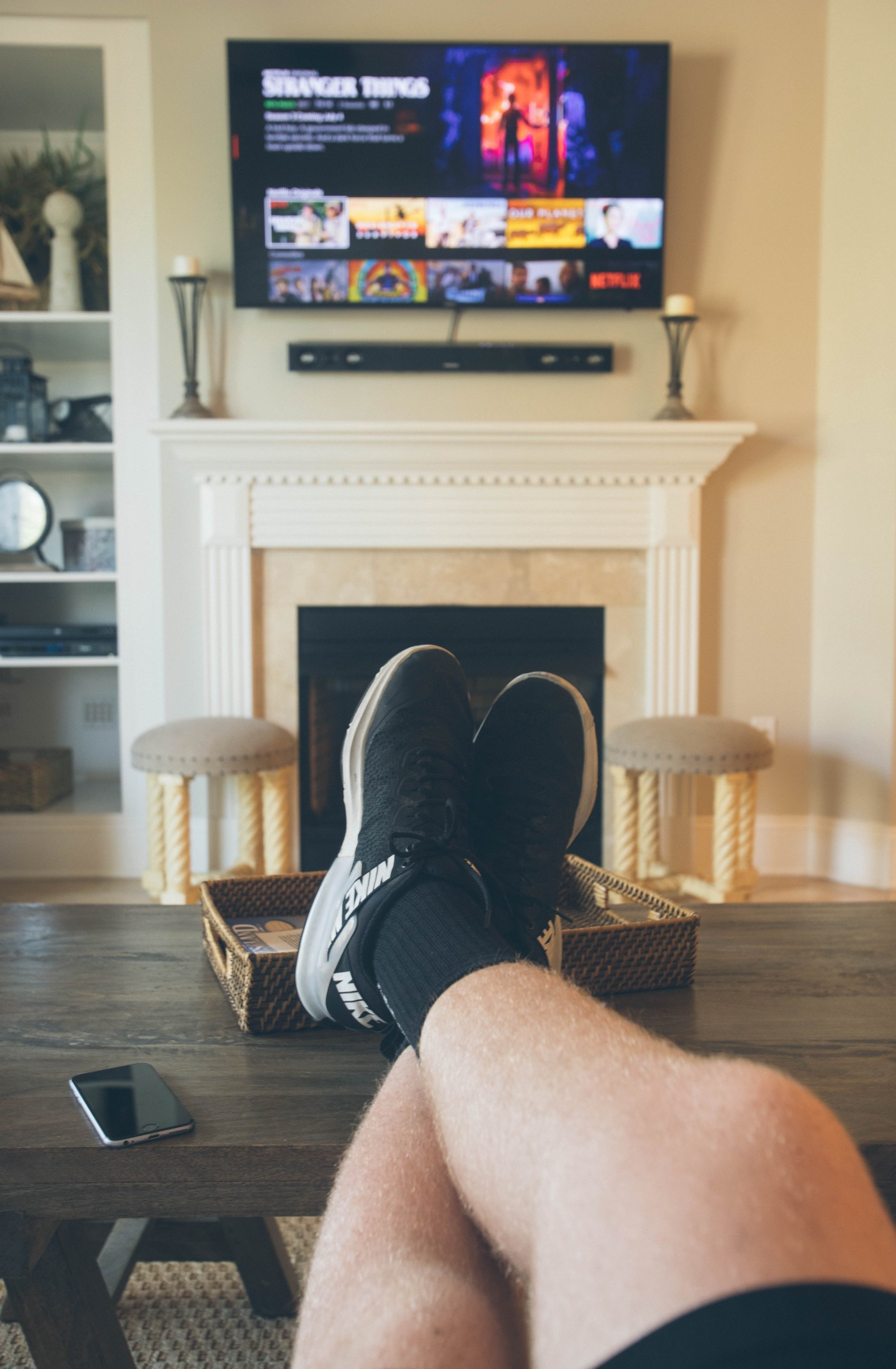Two feet propped on a coffee table in a point-of-view shot of watching Netflix on TV