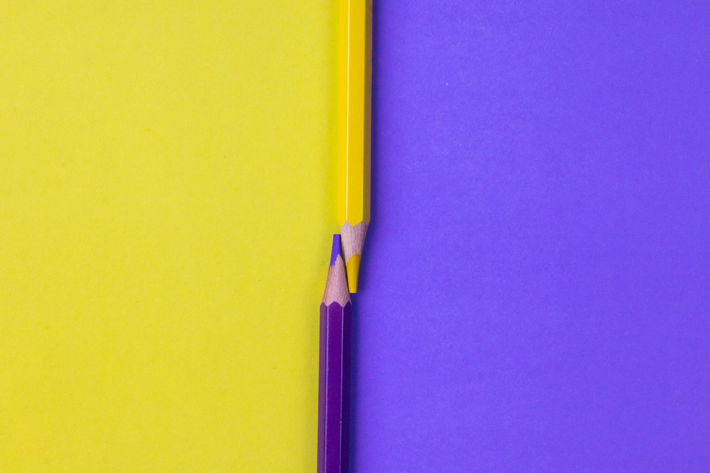 Purple and yellow crayons resting on purple and yellow background