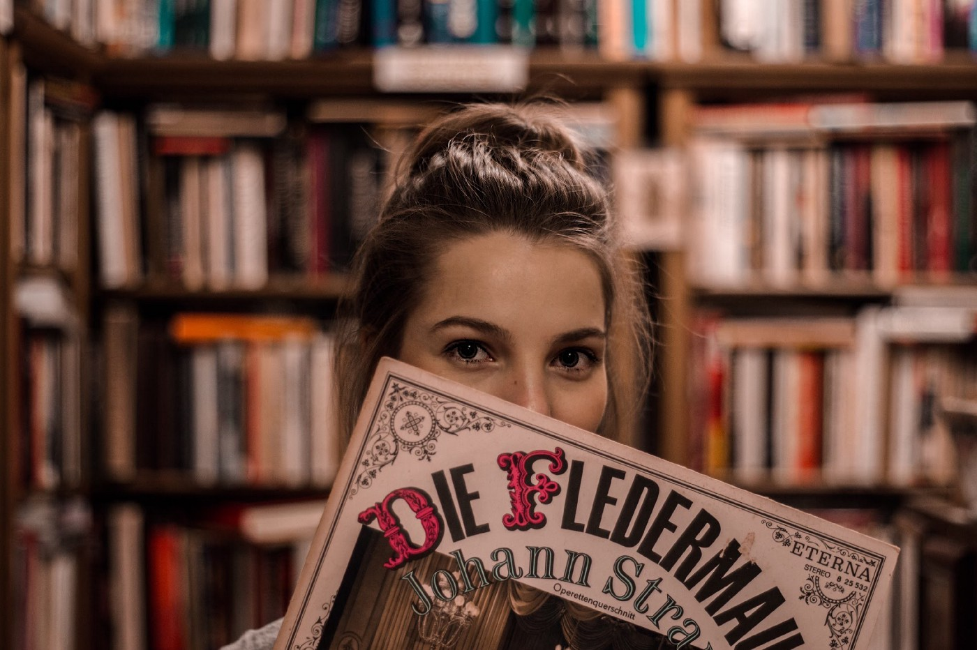 A stock photo of a young woman holding a record of Johann Strauss' Die Fledermaus. Presumably, she is in a library as there is a bookshelf in the background.