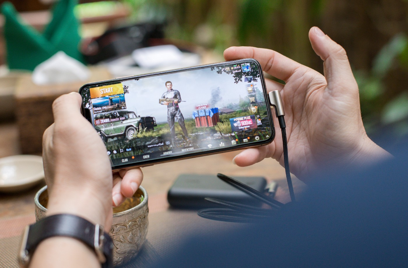 Hands holding a phone in landscape, playing a first person shooter game.
