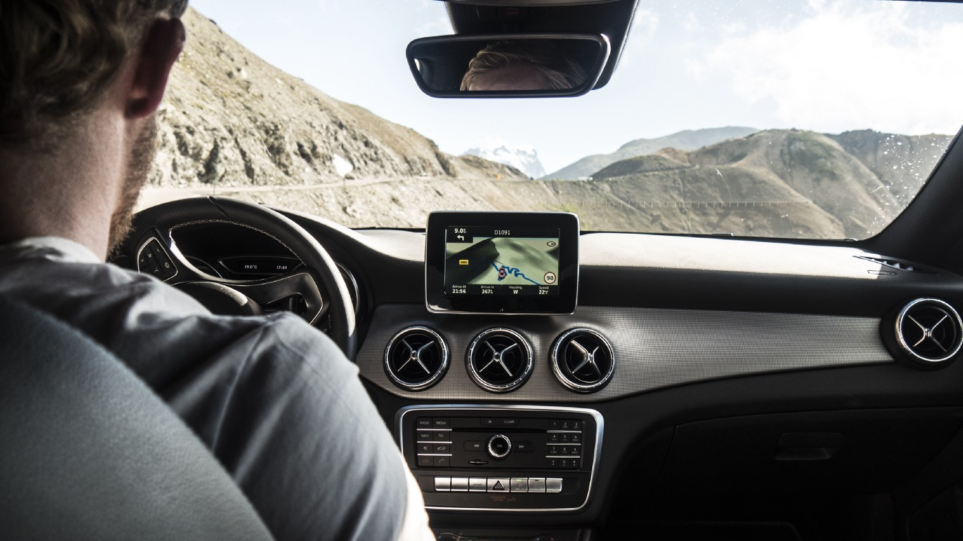Point of view shot of man sitting in the driver's seat of a car driving along the edge of a mountain.