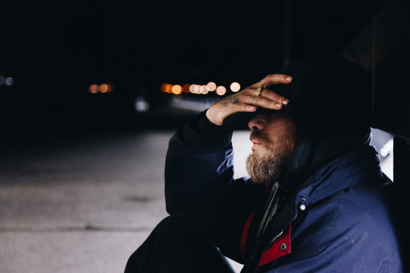Photo of a man sitting on the ground outside at night with his head in his hand.