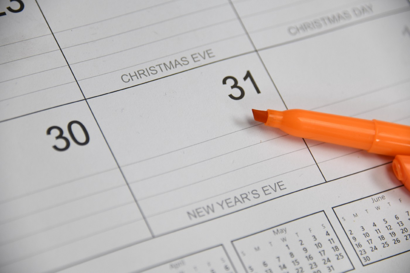 orange highlighter pen pointing at New Year's Eve on a desk calendar