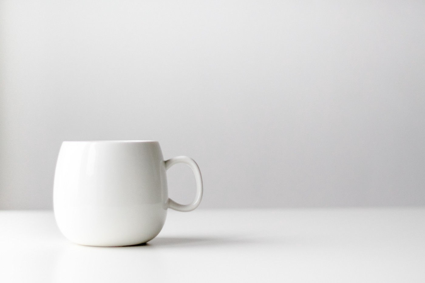 A plain white, seemingly unimportant, coffee mug sits alone on a white table.