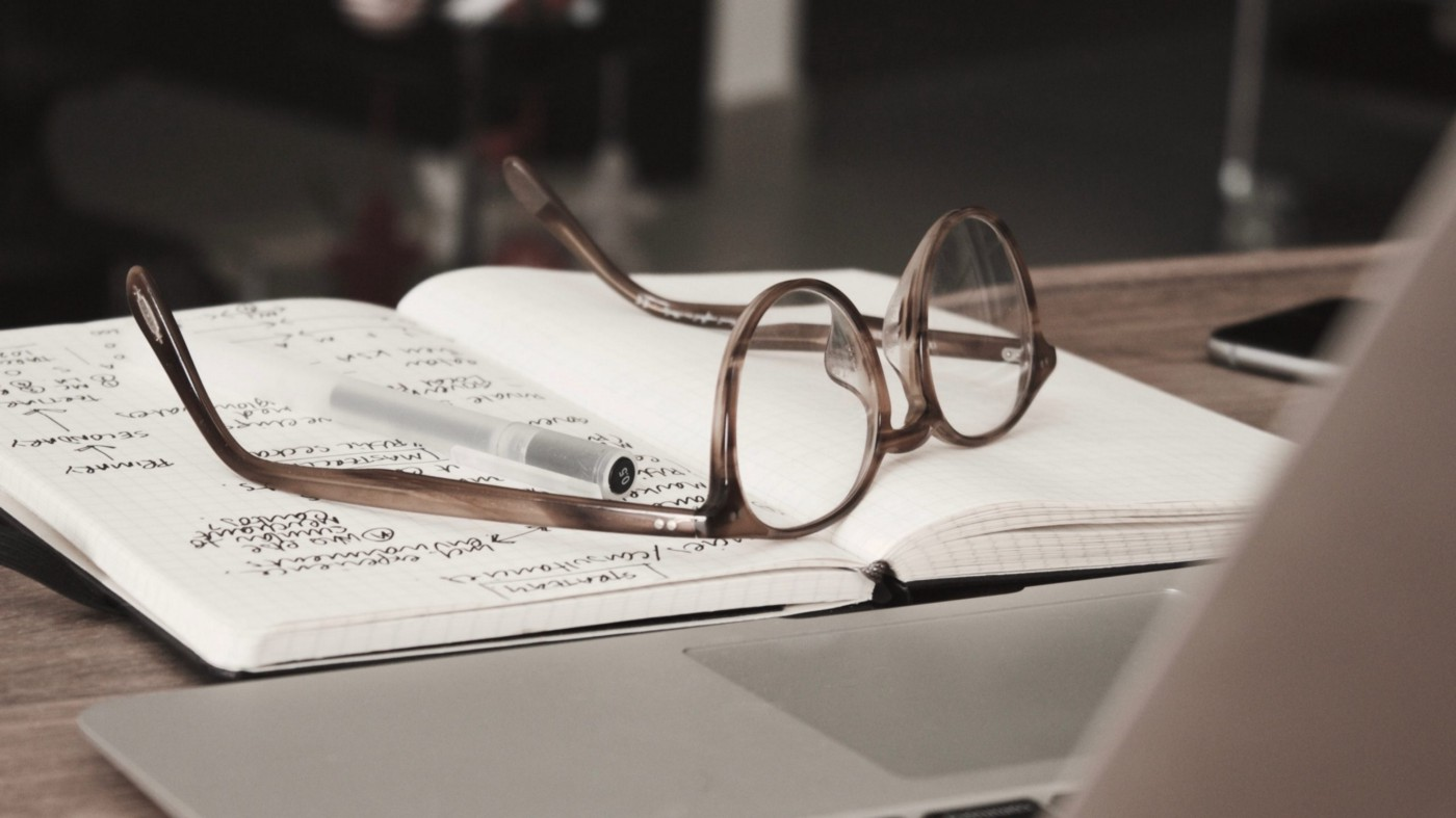 Glasses and a pen on a journal in front of a laptop