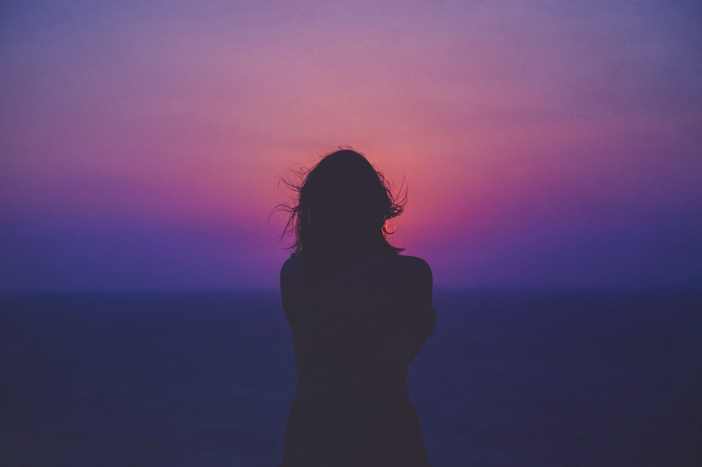 Woman hugs herself while looking out at beautiful sunset.