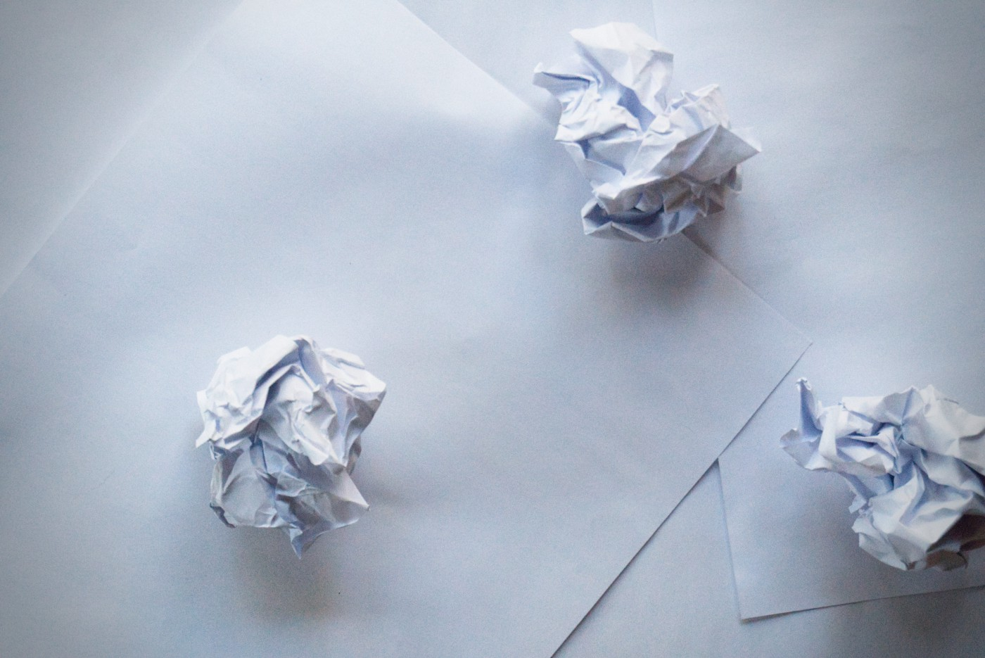 three crumpled pieces of paper on top of two blank sheets of paper