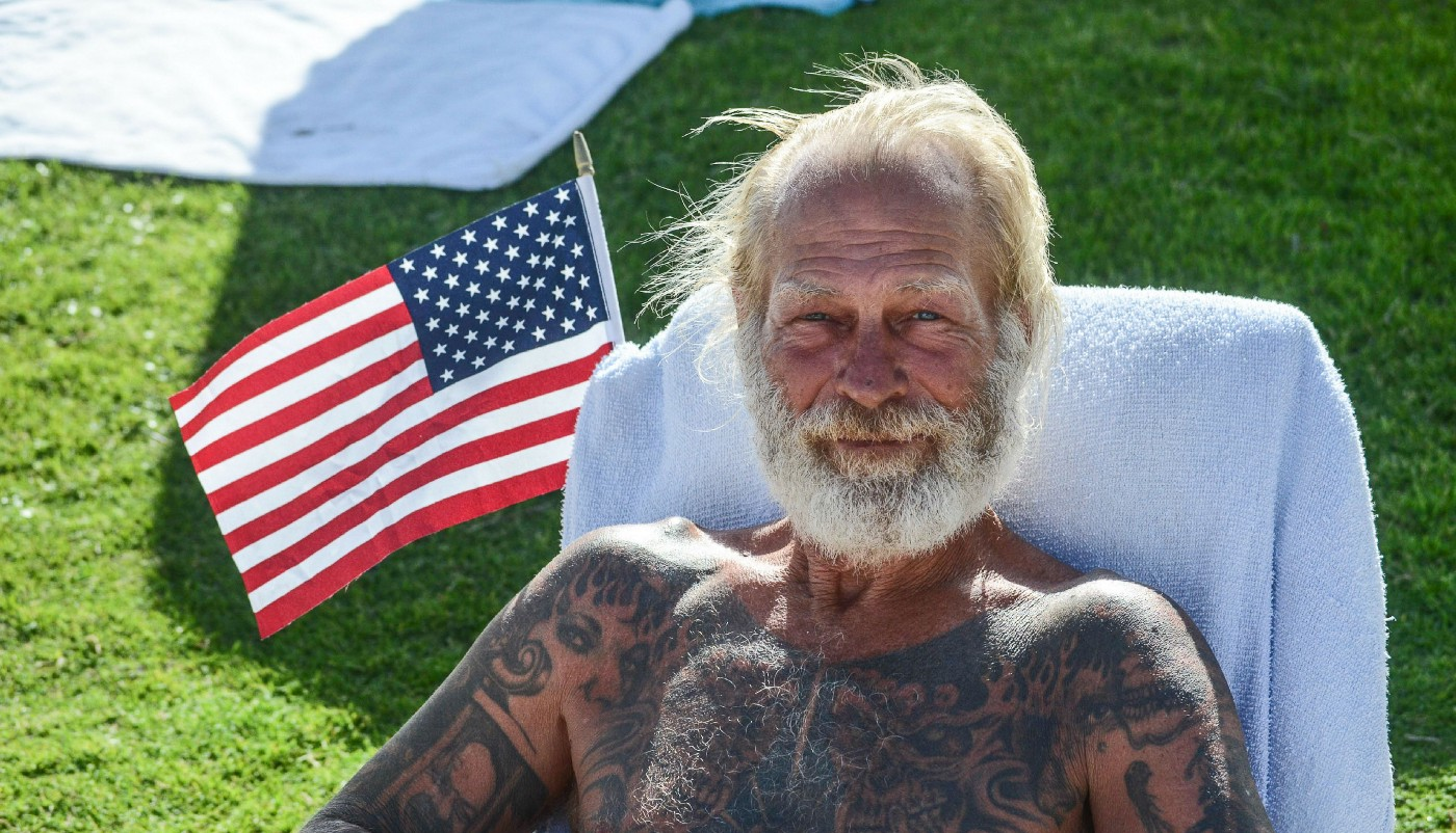 Tattooed man sitting shirtless with American flag behind him.