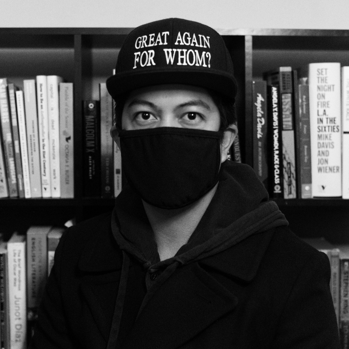 "This is an image of the poet, Michael Guevarra. He is masked, wearing all black and a hat that reads ""Great Again For Whom?"""