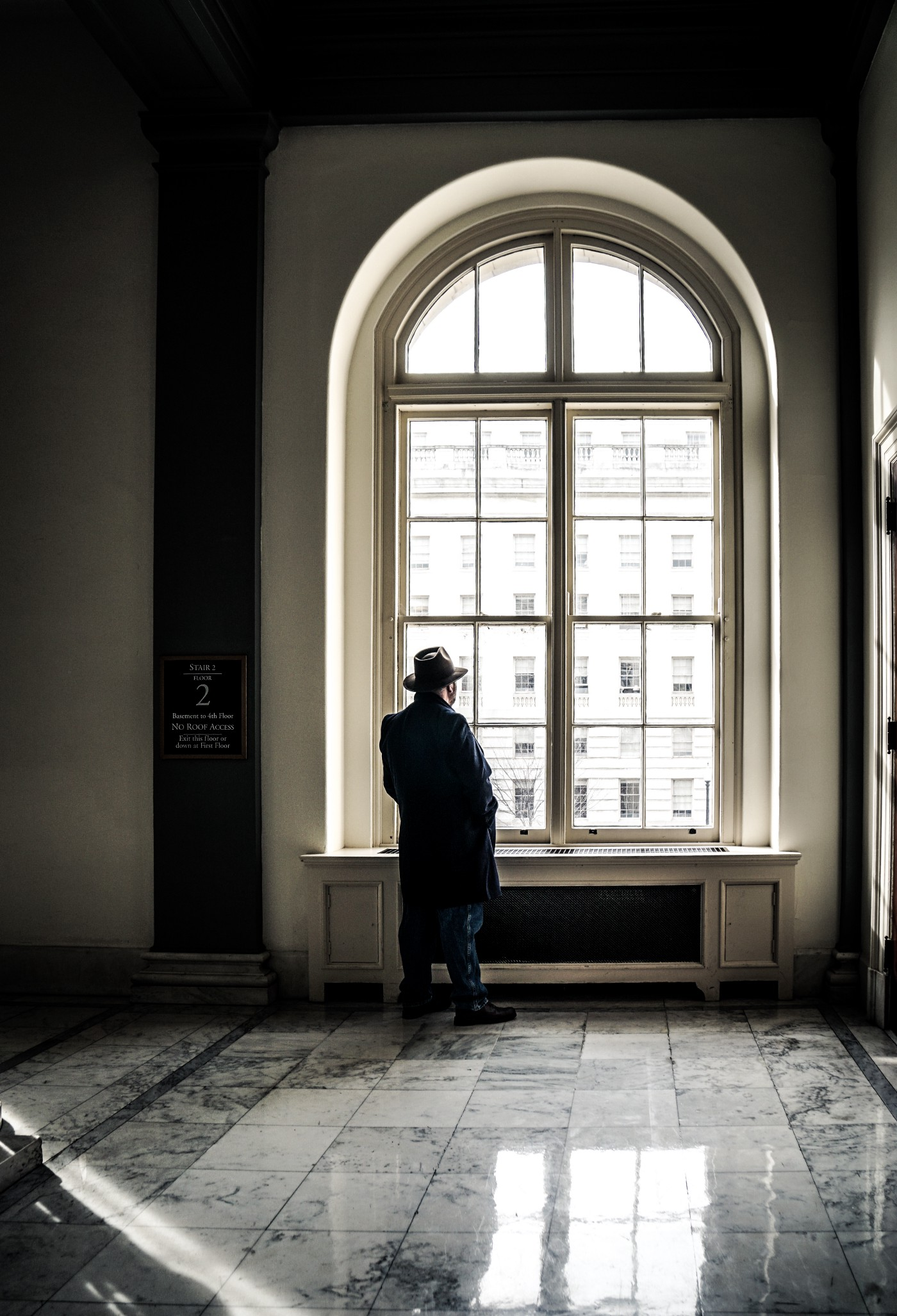 Man with coat and hat, looking outside the window