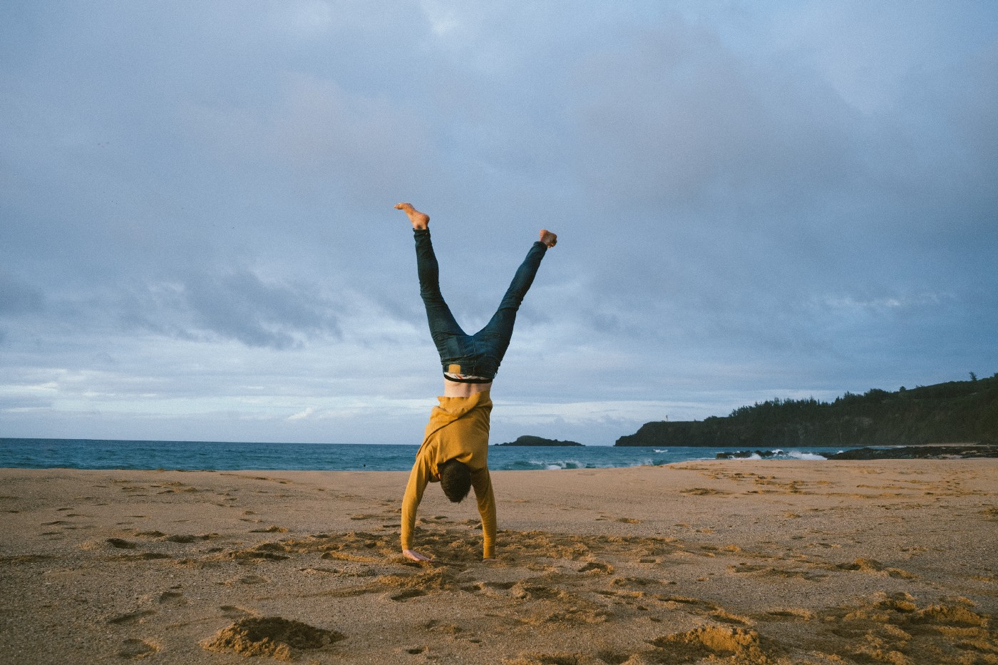 Person doing a cartwheel on the beach.