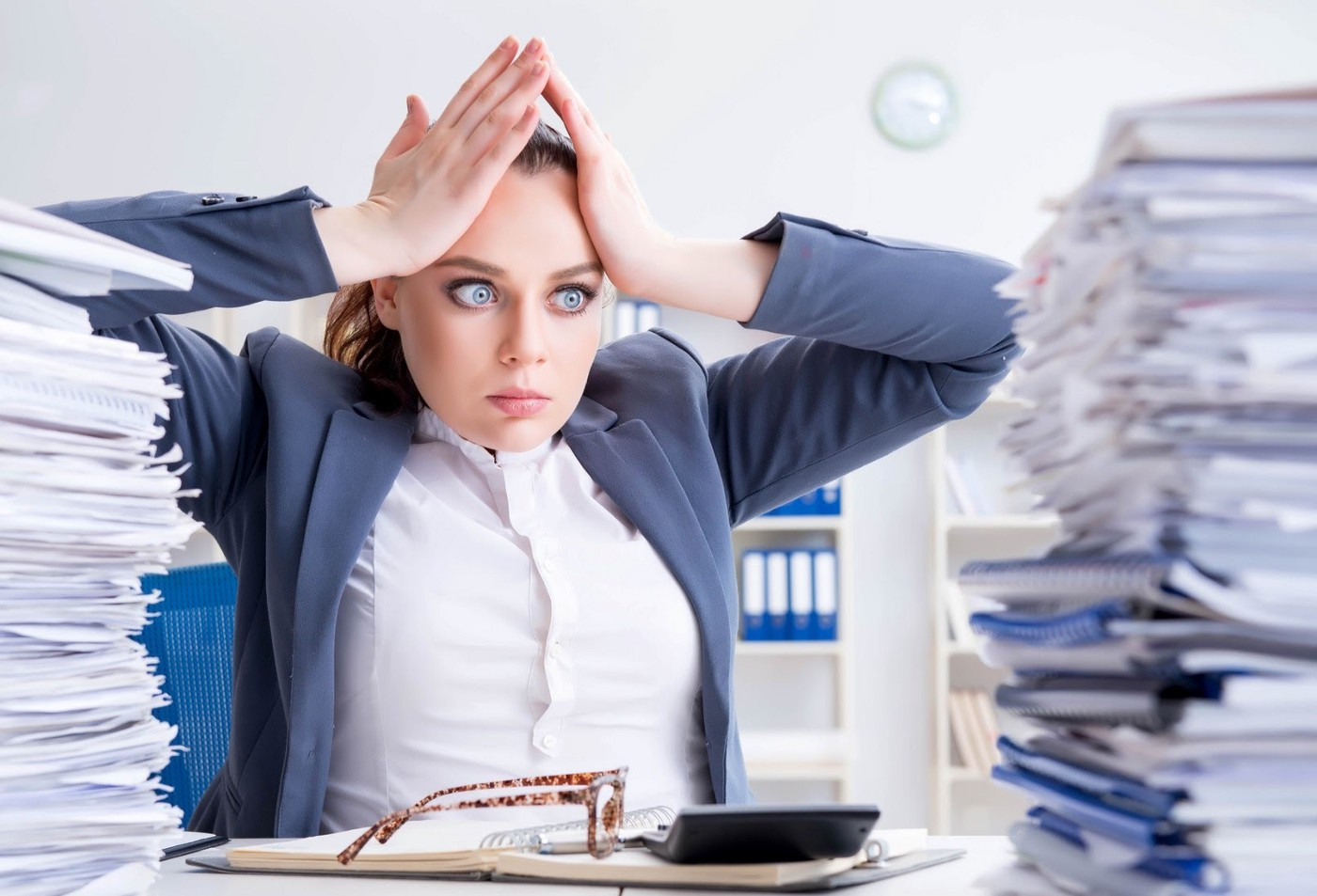 Overworked businesswoman with piles of papers surrounding her