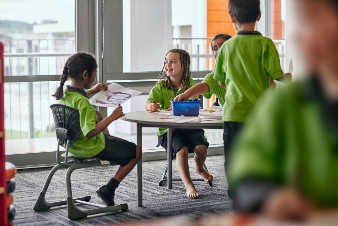 Children in bright green uniform sit and stand around classroom table in New Zealand