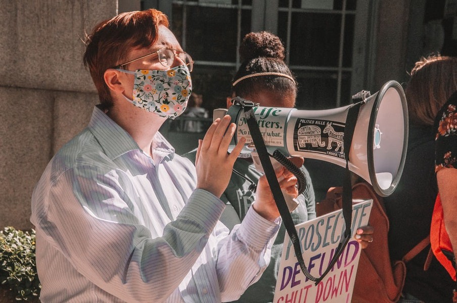 An activist protests in a mask, talking to a megaphone