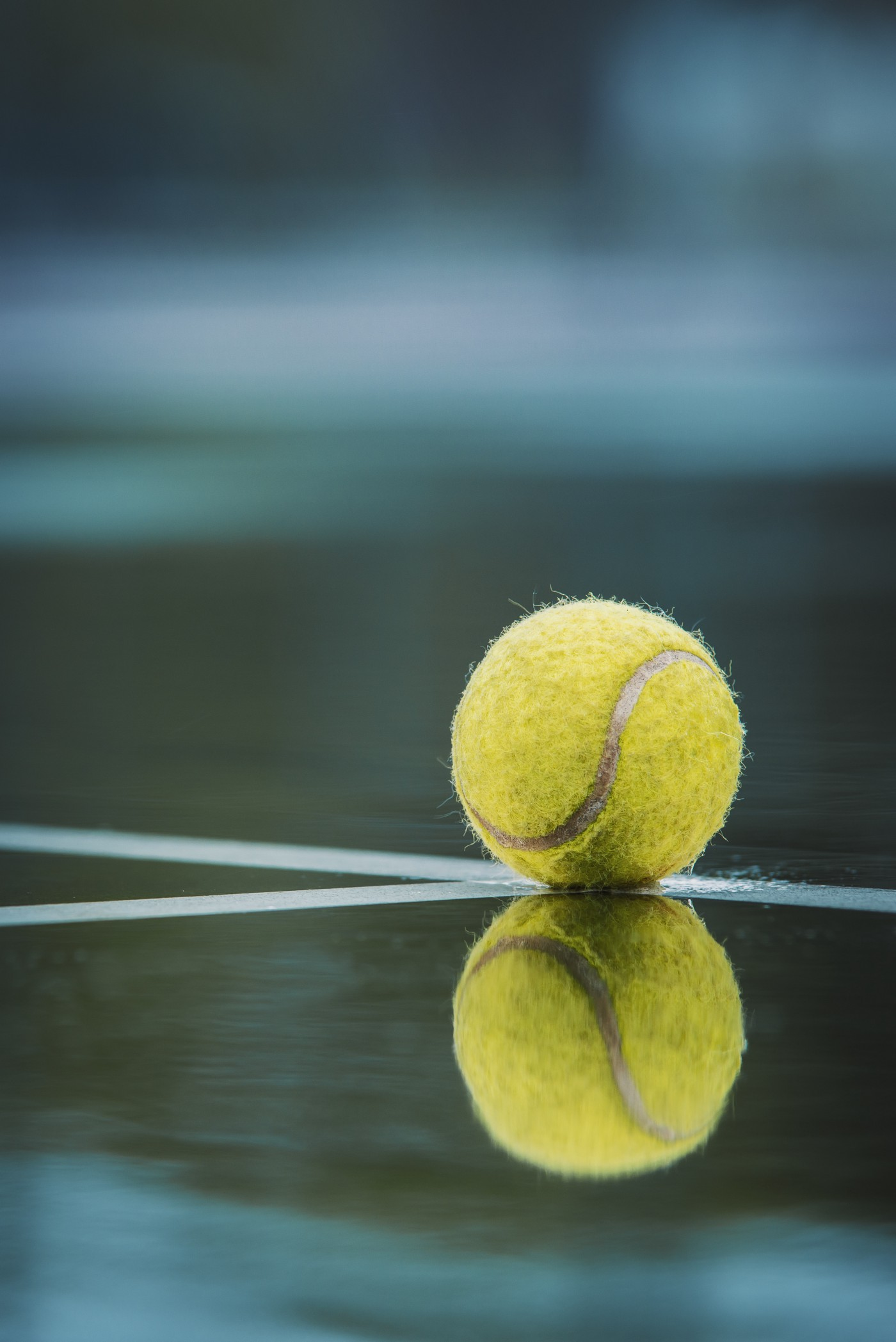 A close-up of a tennis ball landed on the corner intersection of the lines of a court. The court is glassy like a mirror and the clear reflection of the ball on the line is visible.
