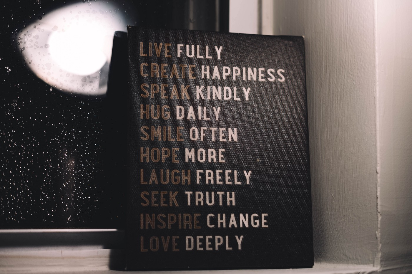A board with positive statements of live fully, create happiness, speaker kindly, hug daily, smile often, hope more, laugh freely, seek truth, inspire change, love deeply