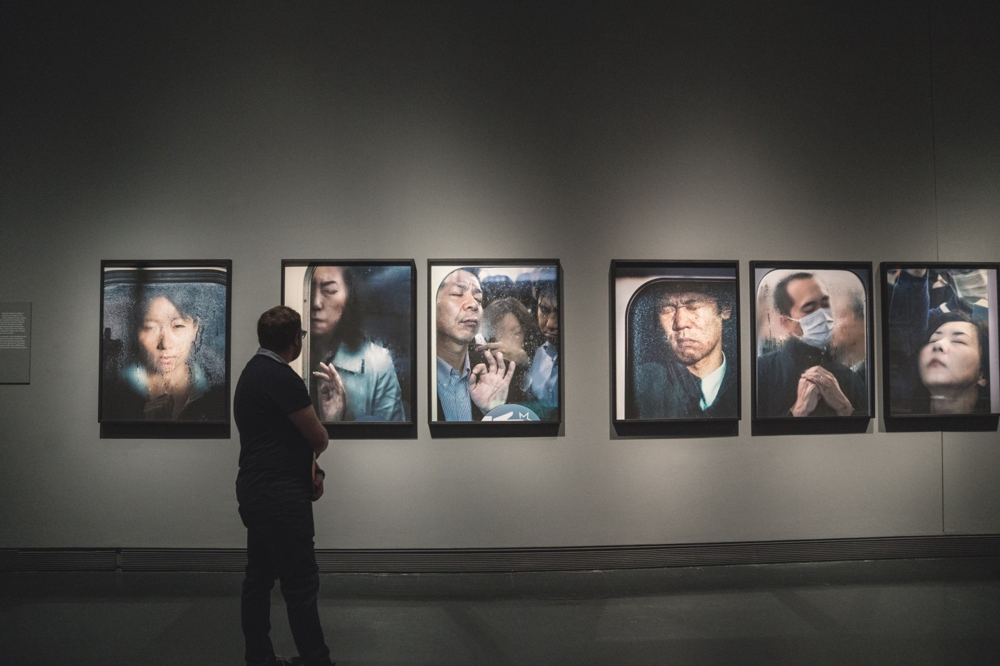 A person looks at images displayed on a wall.