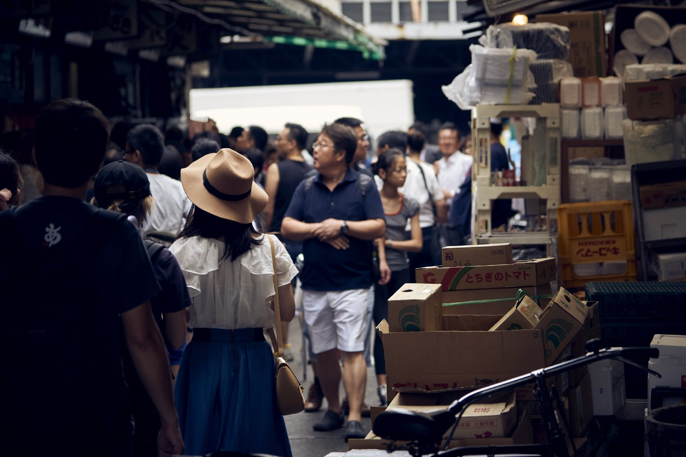 A crowded street filled with people and different boxes placed on the sides.