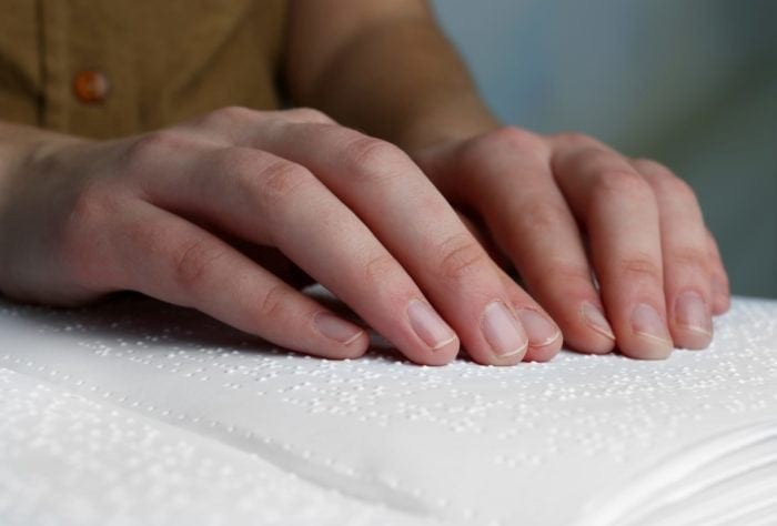 Fingers reading a braille document