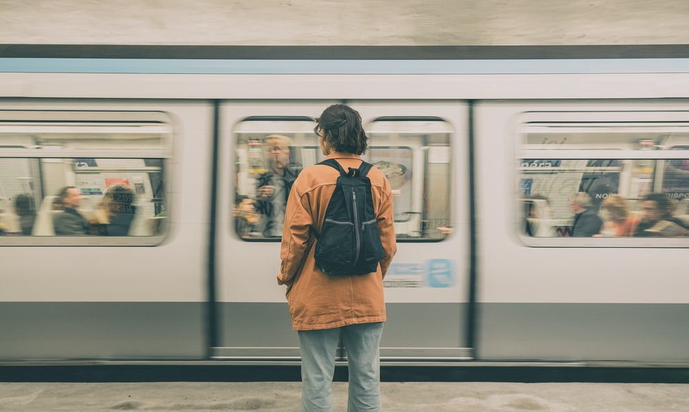 Person with backpack in front of moving train