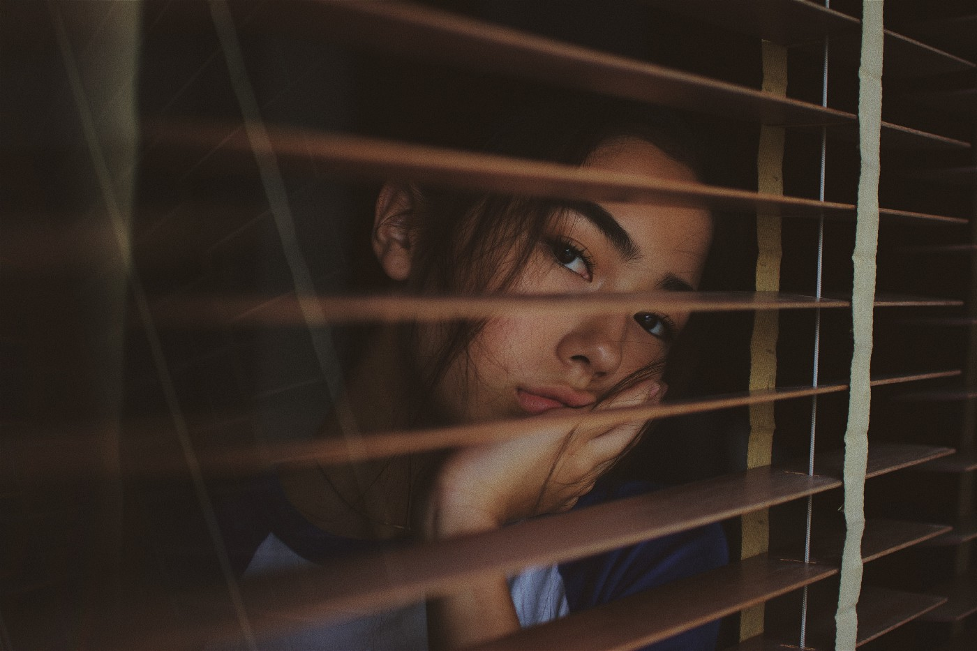 A bored looking girl looking through the blinds.