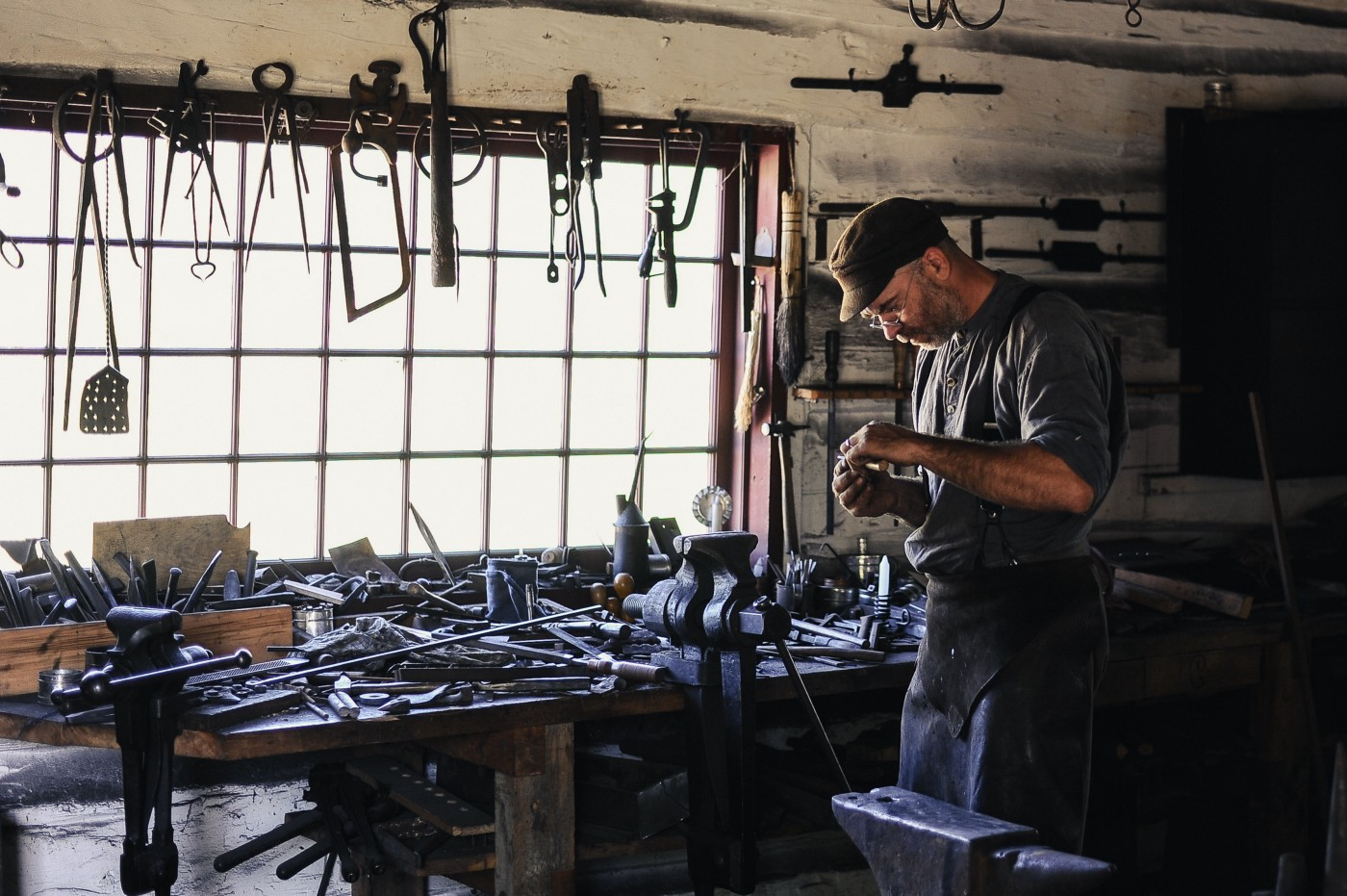 Man wearing leather apron in front of a window. Numerous tools on bench behind him and over the window.