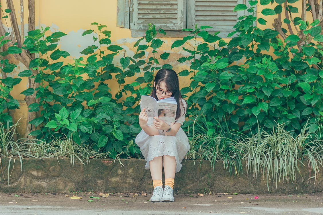 A young person sits on the sidewalk by a bunch of plants, reading. #asian #reading #books