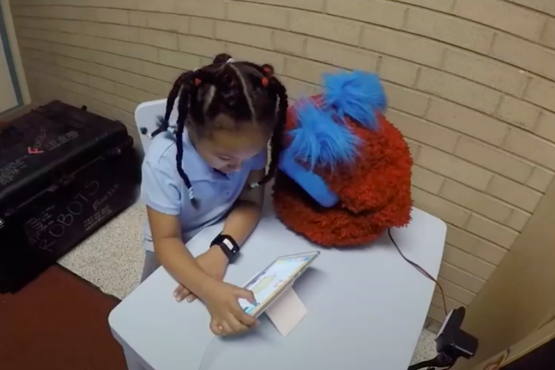 Child does homework with the help of a fluffy robot.