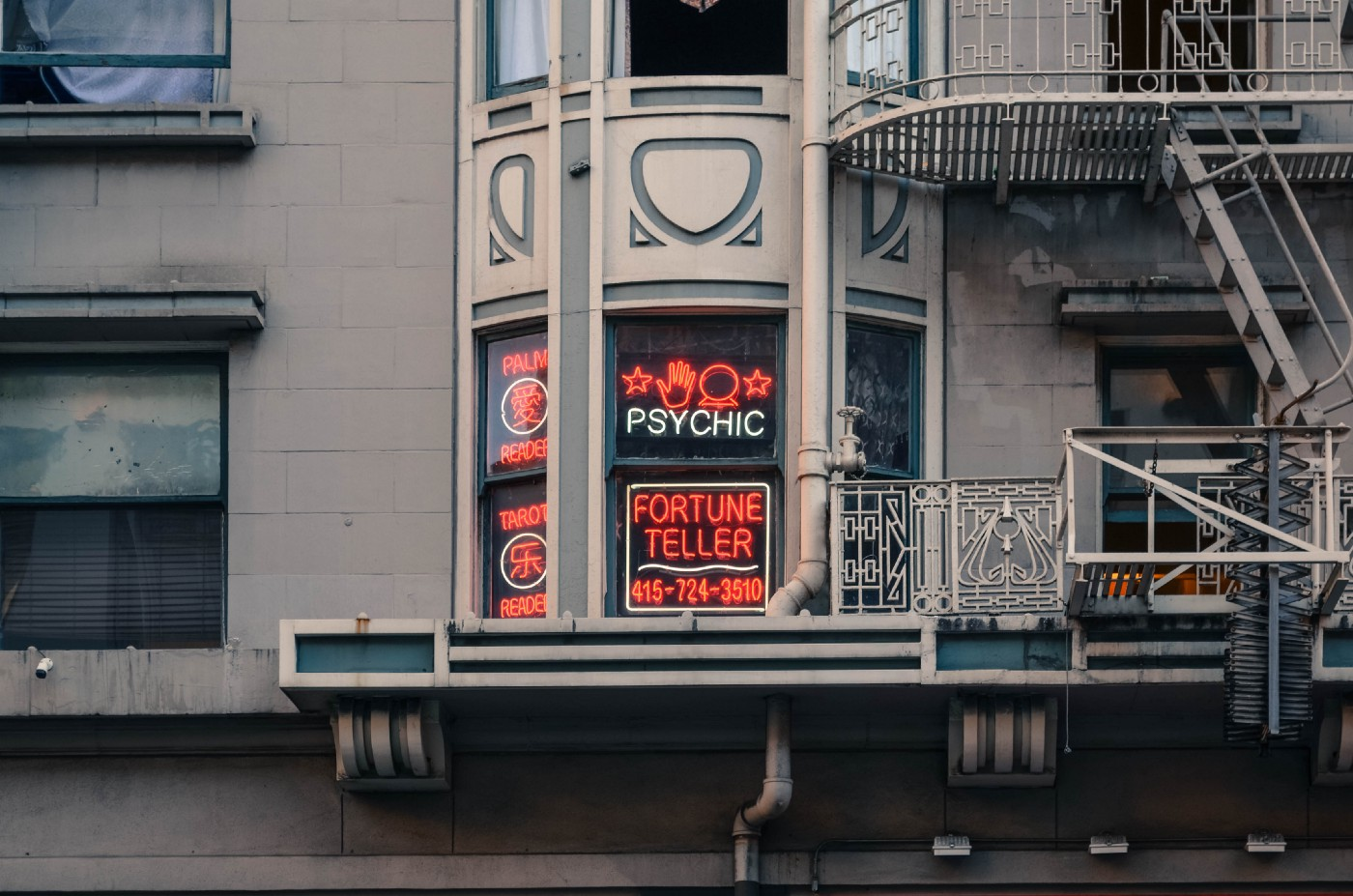 Picture of a window with a neon sign advertising for a psychic reader.