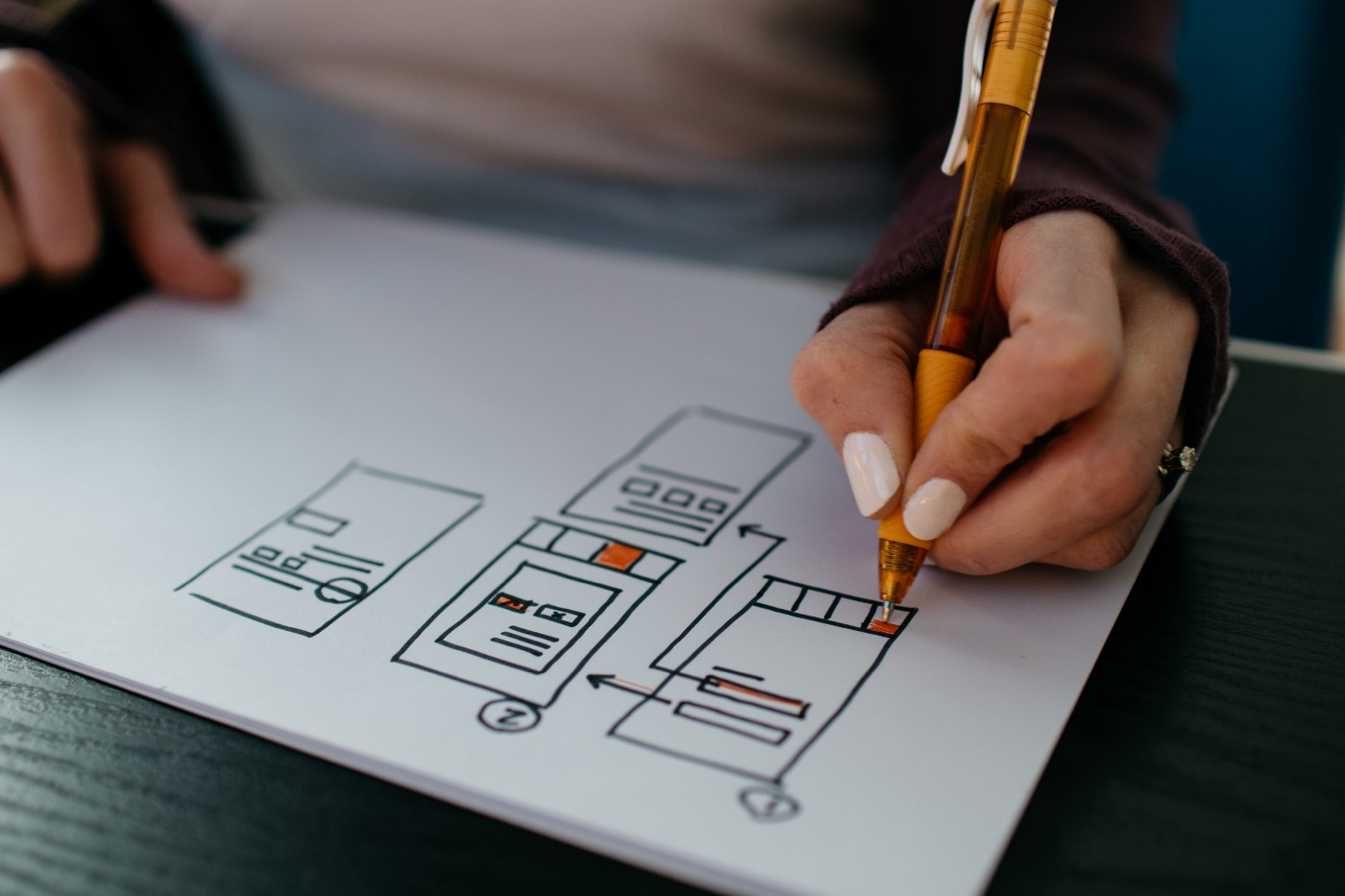 A designer's hand holding a pen, drawing wireframes of a user interface.
