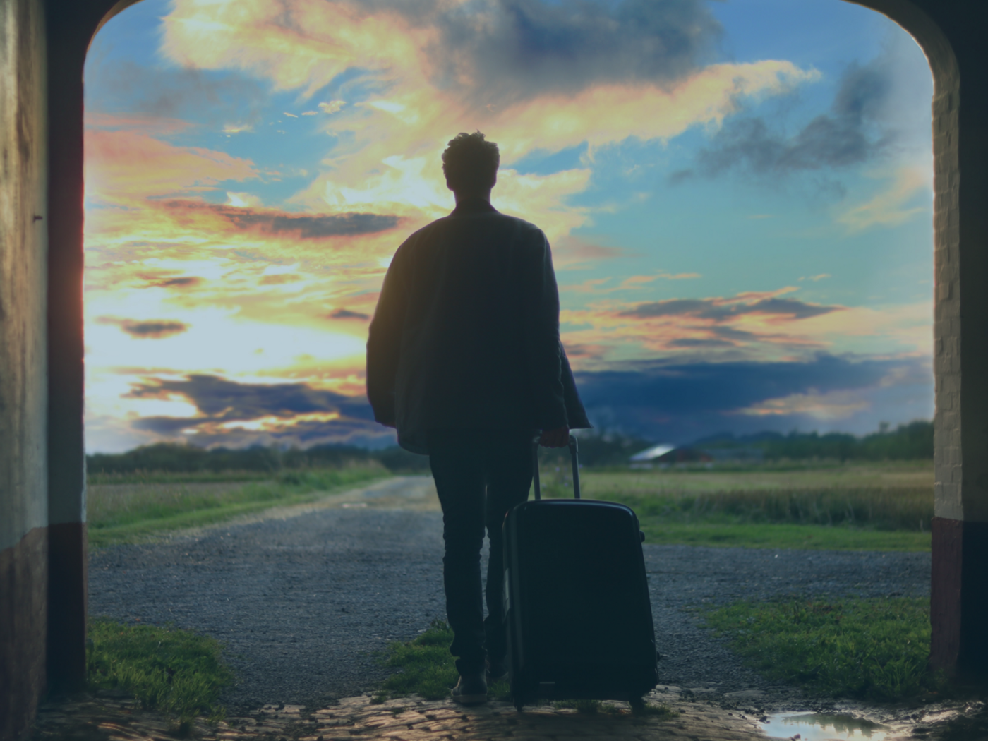 IMAGE IS OF A PERSON WITH A SUITCASE WAKING OUT INTO THE OUTDOORS WITH A BEAUTIFUL SKYSCAPE IN FRONT OF THEM.