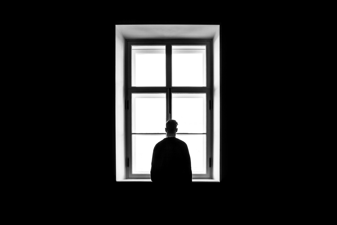 stark black-and-white picture of a man with slumped shoulders looking out a window