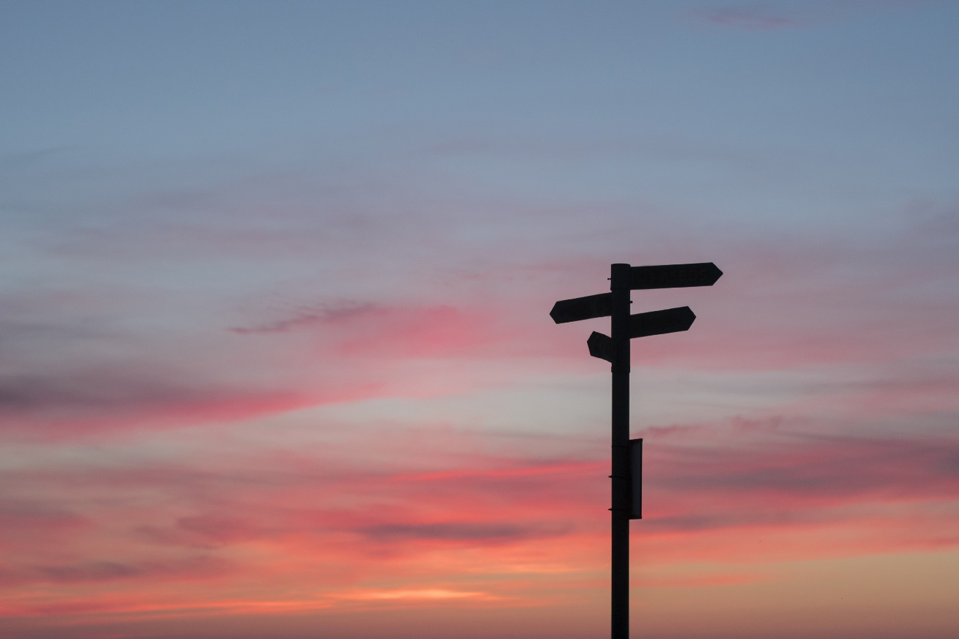 signpost with arrows pointing in several directions, against a sunset sky