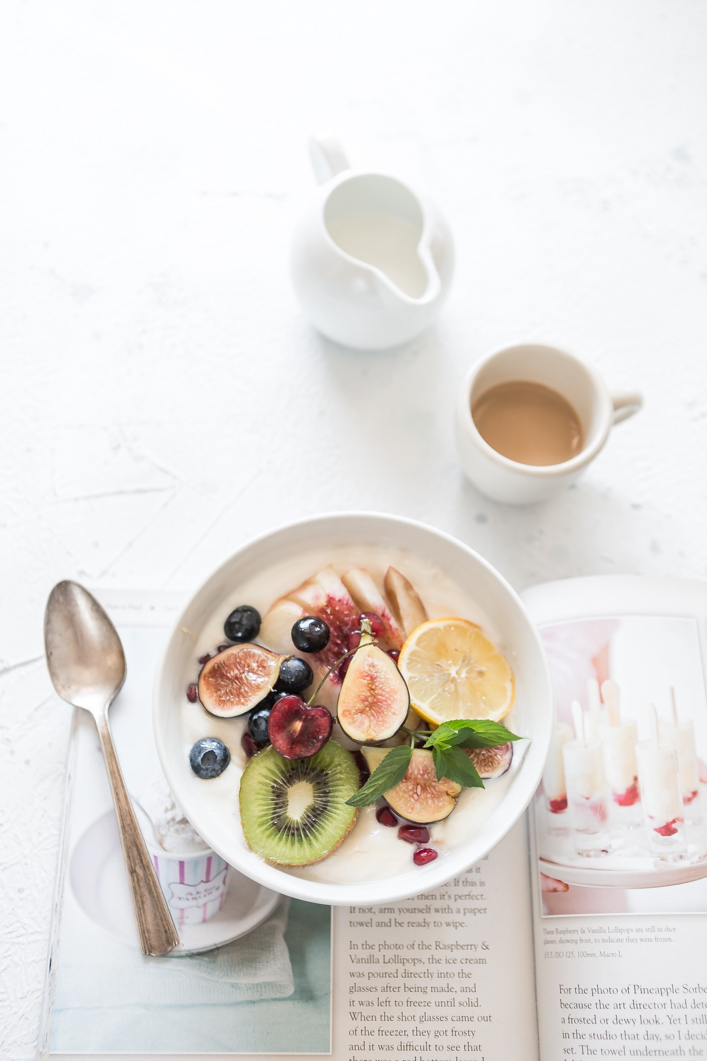 a bowl of yogurt with sliced fruit on top, a cup of espresso and a small bit of milk for the coffee. The bowl is sitting on top of an open magazine showing an article and photos of yogurt-based foods.