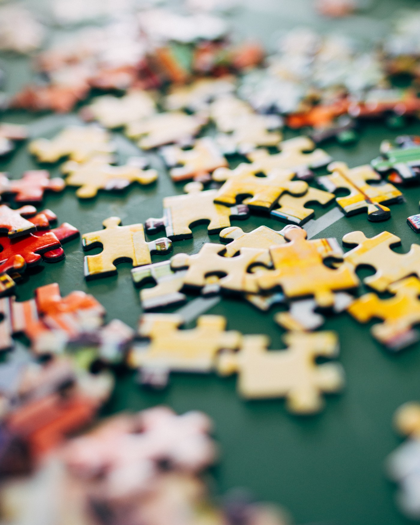 A picture of loose yellow colored jigsaw puzzle pieces