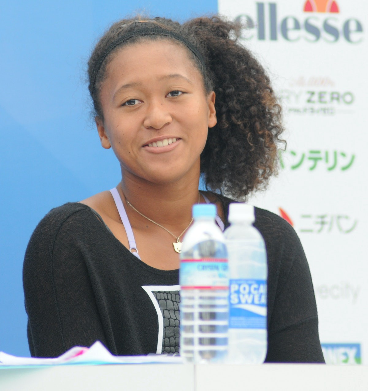 photo of tennis player Naomi Osaka sitting at a table with 2 water bottles.