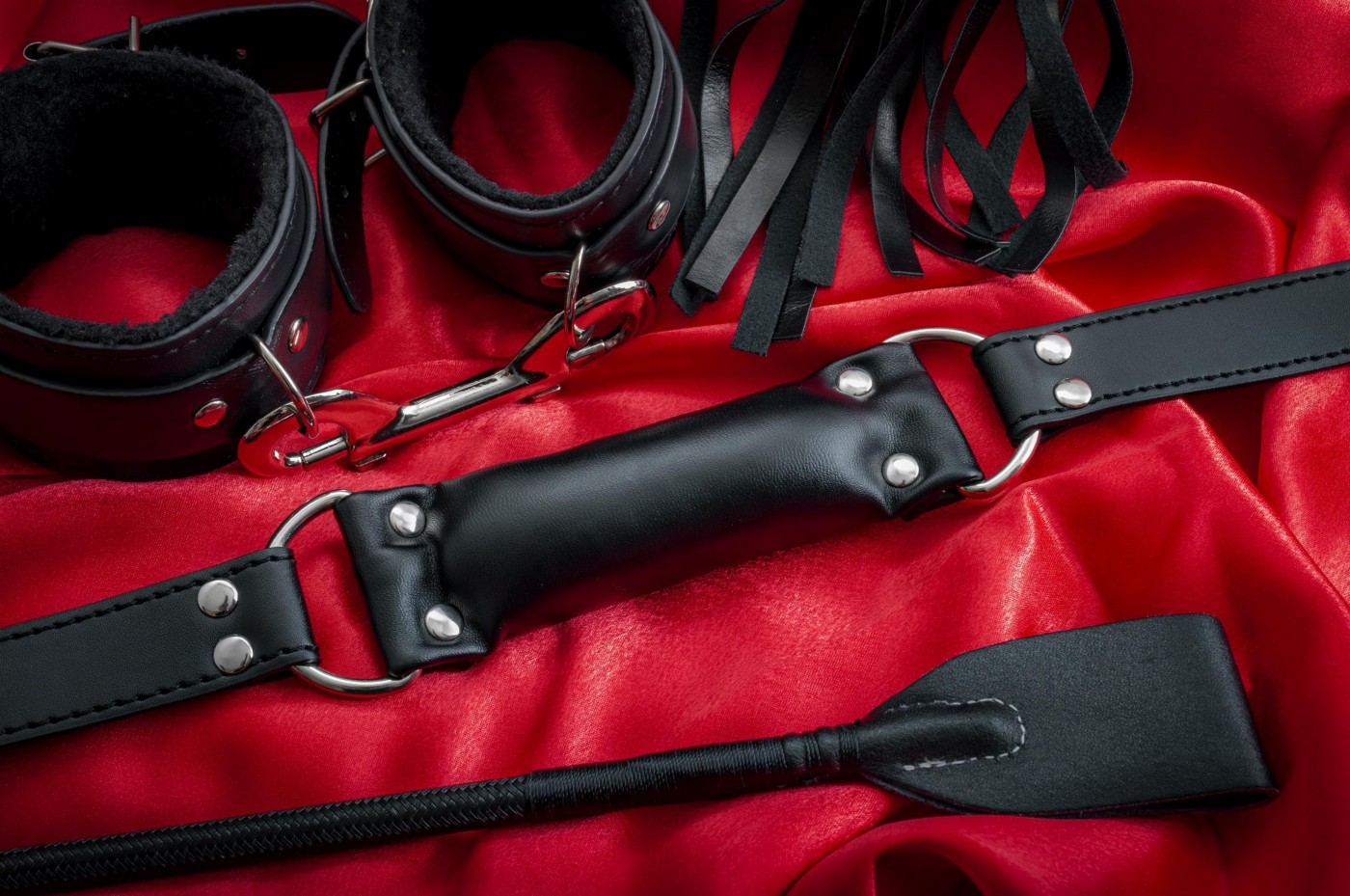 BDSM toys on red sheets