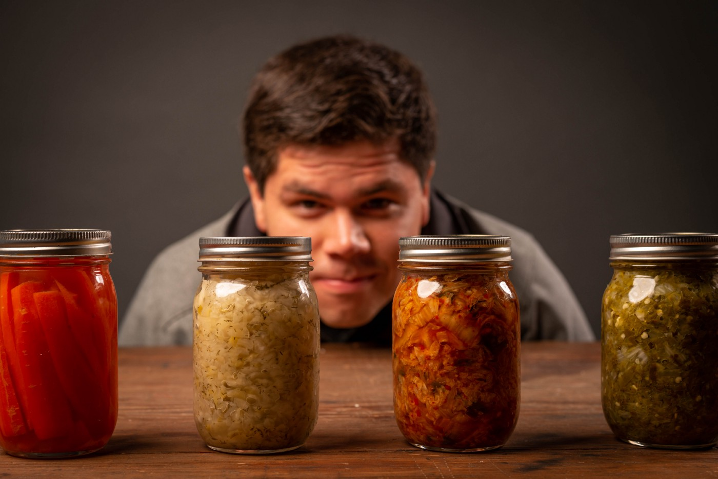 A man staring a four jars of pickles