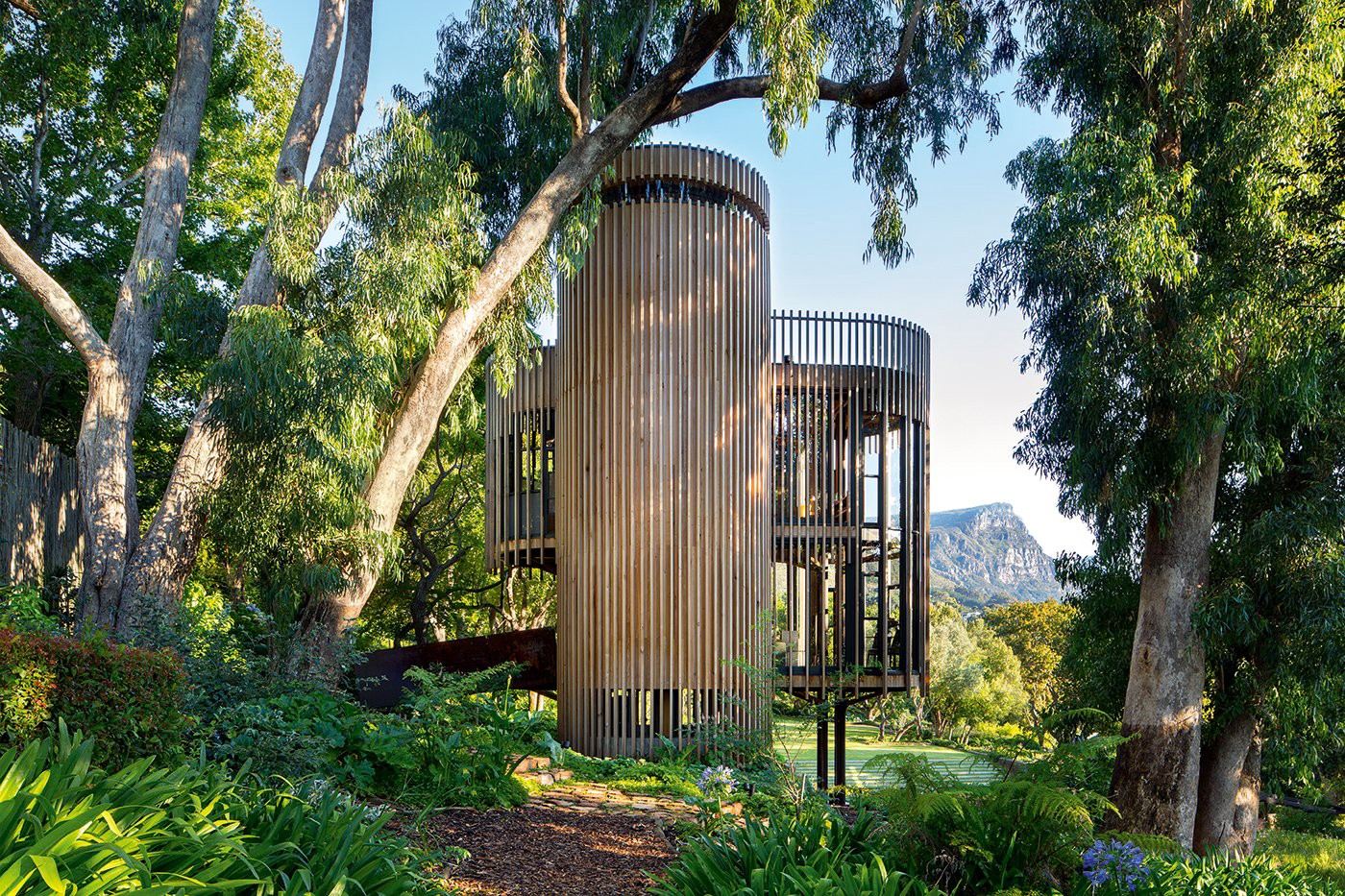 """The timber slats on the facade of Tree House Constantia are untreated and have been left to weather naturally, creating a rustic aesthetic. With an entire """"wall"""" made of glass, the cabin's occupants can enjoy the most spectacular, uninterrupted views of the open countryside. (Photo: Adam Letch, Beyond the West)"""