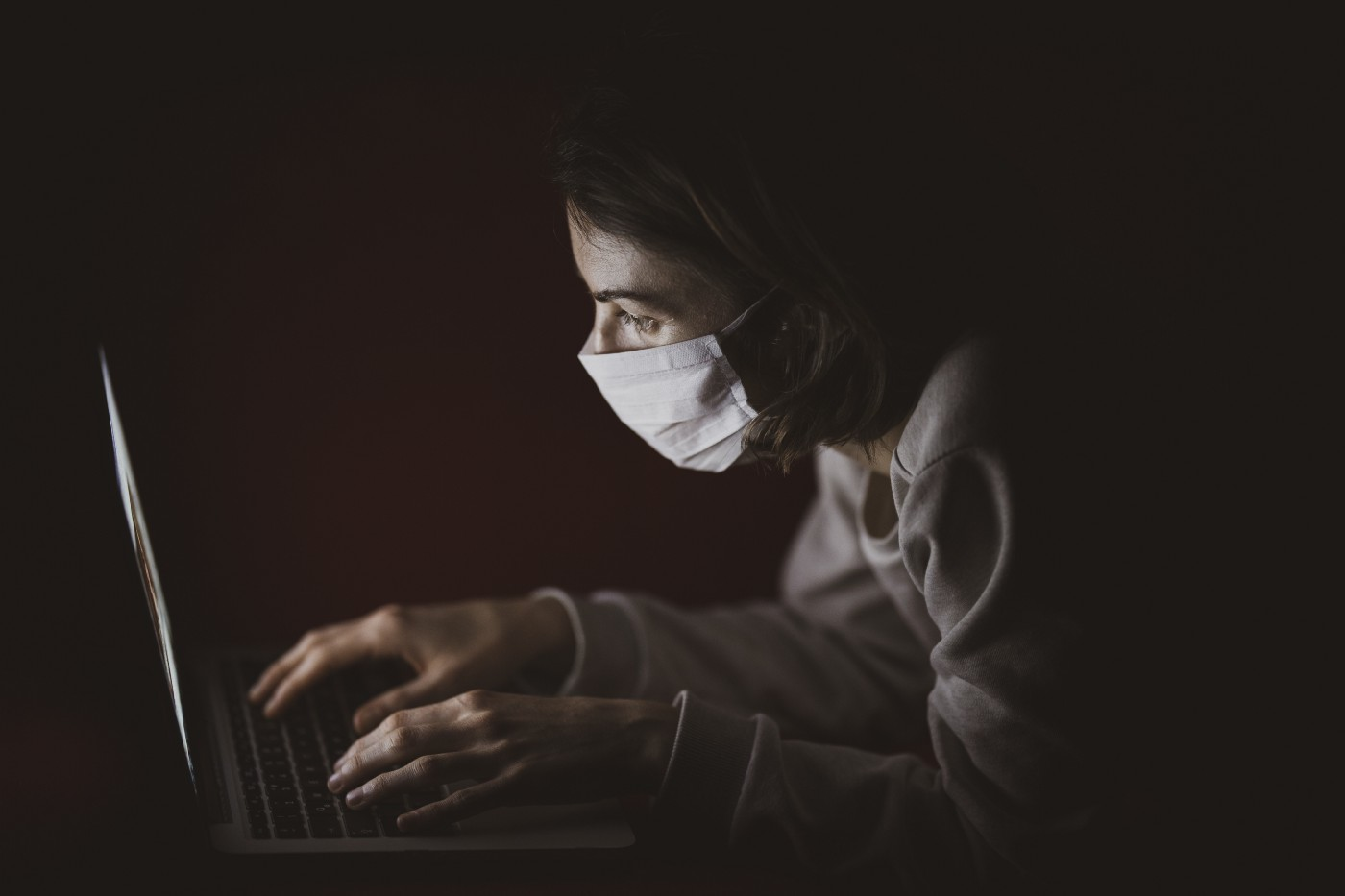 A woman wearing a mask typing on a laptop in the dark