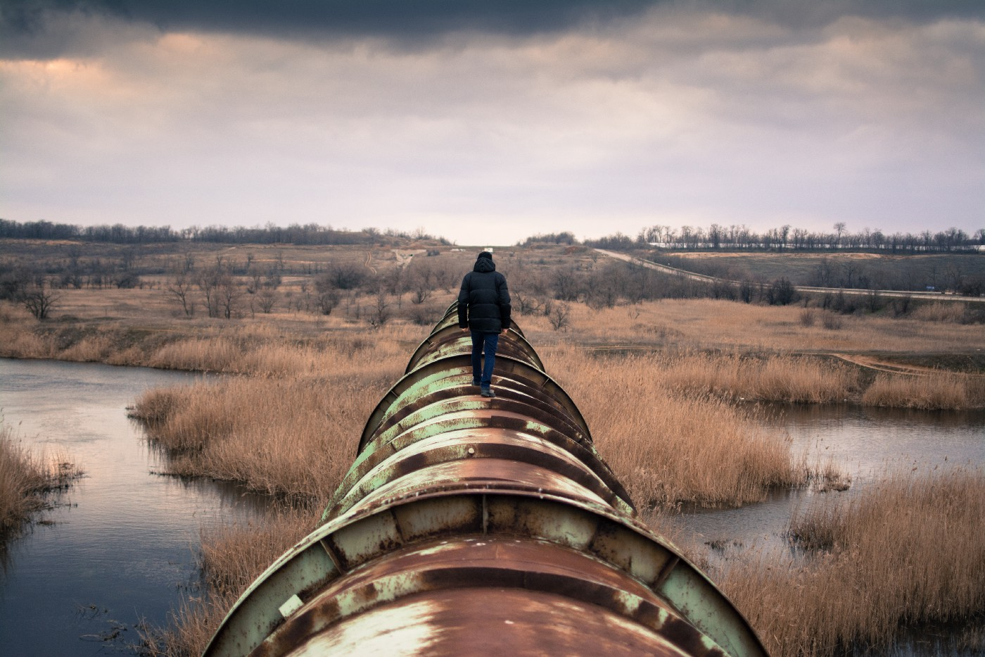 person walking along an above-ground pipeline through a marsh